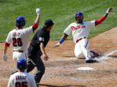 Domonic Brown of the Philadelphia Phillies scores after Chase Utley on a tworun double by Wil Nieves during the fifth inning in a game against the...