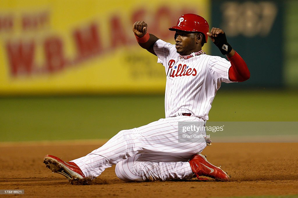 Domonic Brown #9 of the Philadelphia Phillies slides into third base in the sixth inning of the game against the Washington Nationals at Citizens Bank Park on July 11, 2013 in Philadelphia, Pennsylvania.