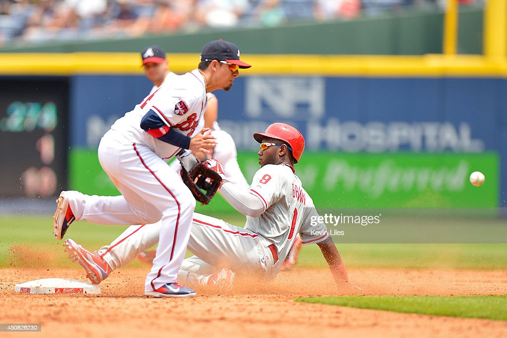 <a gi-track='captionPersonalityLinkClicked' href=/galleries/search?phrase=Domonic+Brown&family=editorial&specificpeople=6900643 ng-click='$event.stopPropagation()'>Domonic Brown</a> #9 of the Philadelphia Phillies steals second base as <a gi-track='captionPersonalityLinkClicked' href=/galleries/search?phrase=Ramiro+Pena&family=editorial&specificpeople=809222 ng-click='$event.stopPropagation()'>Ramiro Pena</a> #14 of the Atlanta Braves waits on the ball during the sixth inning at Turner Field on June 18, 2014 in Atlanta, Georgia. The Braves won 10-5.