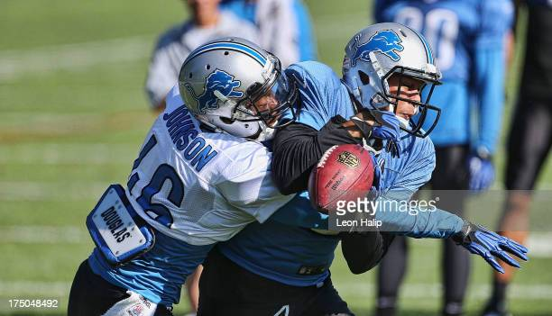 Domonique Johnson and Matt Willis of the Detroit Lions battle for the ball during training camp on July 30 2013 in Allen Park Michigan