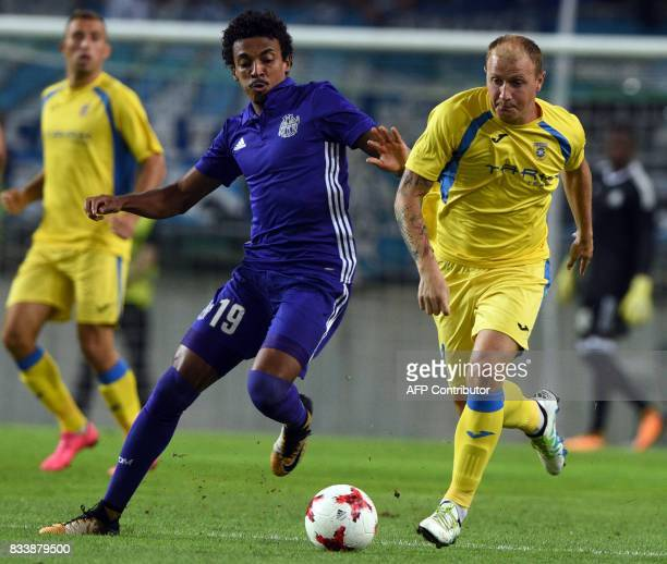 Domzale's Senijad Ibricic and Marseille's Luiz Gustavo vie for the ball during the UEFA Europa League playoff round football match NK Domzale vs...