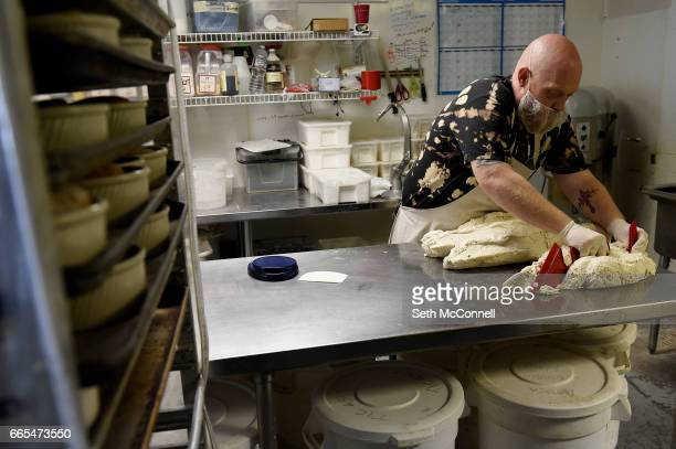 Don Allen cuts dough into sections before weighing out and balling the dough for french bread loaves at Gluten Free Things on April 5 in Arvada...
