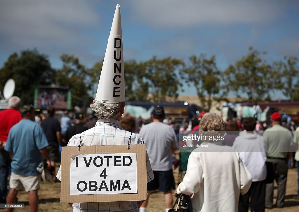 Don Bahl wears a dunce hat and a sign stating that he voted for US President Barack Obama during the Tea Party Express tour kickoff on August 27 2011...