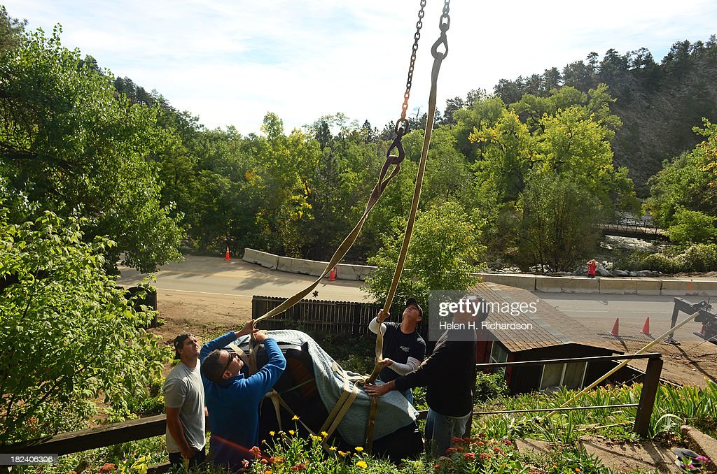 Don Gulbrandson, second from right, owner of Bob's Piano Sales and Service, helps his crew to watch for high voltage power lines above as they secure a 1933 Mason & Hamlin grand piano to chains from a crane parked below on Canyon Blvd in Boulder, Co on September 29, 2013. Piano teacher Carolyn Meyer, not shown, lost her house to the recent floods that ravaged Boulder county and 13 other counties in Colorado. The piano miraculously survived the flooding and mudslides that overtook the house. The piano weighs about 1,000 lbs and will be kept in storage until Carolyn finds a new place to live. The other workers are from left to right: Greg Newham, in blue, Gavin Geis, and Fallon Wacasey, right.