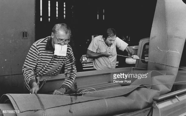 Don Harder with paper work in his ***** gets a helping hand from Bob Barnes of American Furniture Co loading carpet onto the back of his pickup truck...