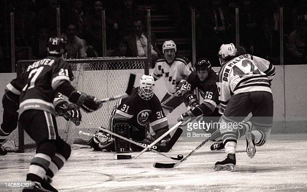 Don Maloney of the New York Rangers goes for the puck as goalie Billy Smith and Dave Langevin of the New York Islanders defend the net during Game 3...