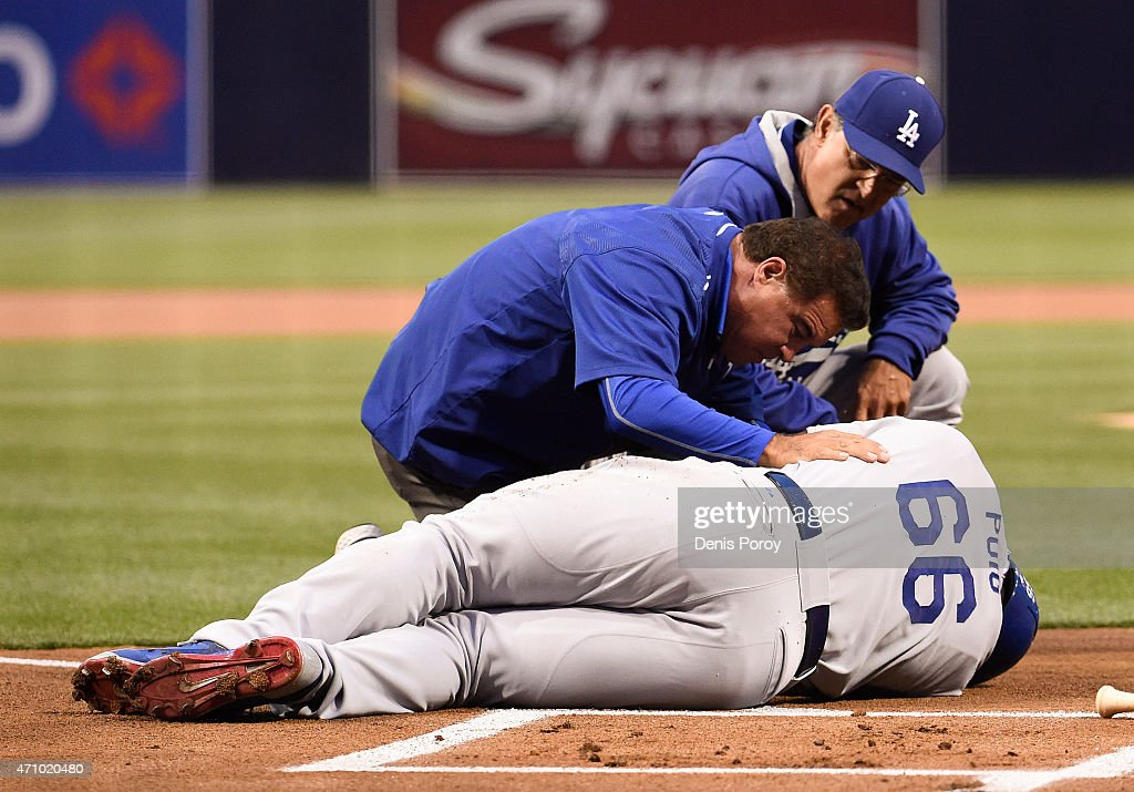 Don Mattingly #8 of the Los Angeles Dodgers (R) and a trainer tend to Yasiel Puig #66 of the Los Angeles Dodgers after being hit with a pitch during the first inning of a baseball game against the San Diego Padres at Petco Park April 24, 2015 in San Diego, California. Puig played out the inning.