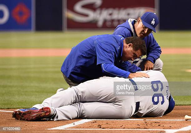 Don Mattingly of the Los Angeles Dodgers and a trainer tend to Yasiel Puig of the Los Angeles Dodgers after being hit with a pitch during the first...