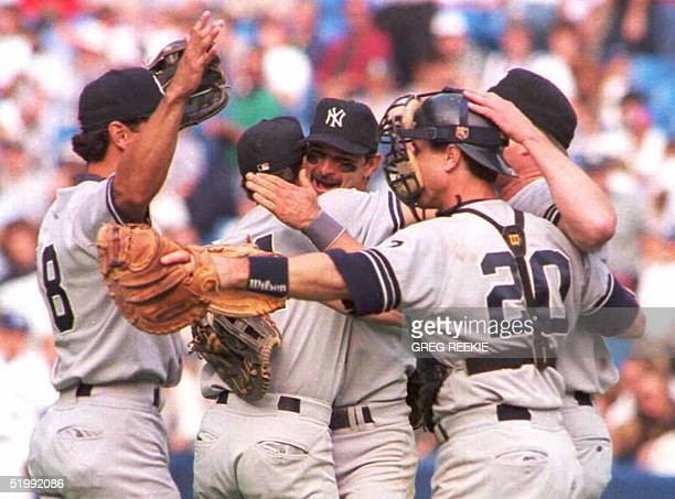 Don Mattingly of the New York Yankees hugs teammate Pat Kelly as outfielder Ruben Rivera and catcher Mike Stanley join the celebration after the...