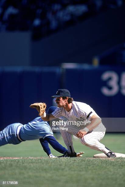 Don Mattingly of the New York Yankees prepares to receive a throw on a pickoff attempt as the base runner dives back to first base during a 1985...