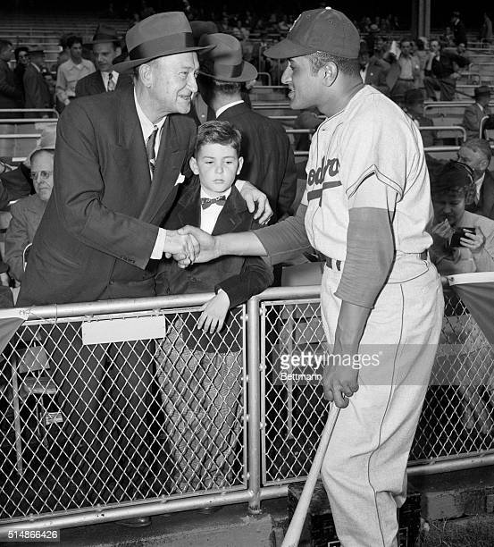 Don Newcombe the Brooklyn Dodgers starting pitcher for the first game of the 1949 World Series shakes hands with Hall of Famer Ty Coob With Cobb is...