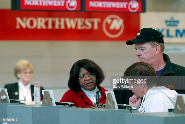 Don Robertson and his wife Sandra Robertson check in to their Northwest Air Lines flight back home to Canada with the help of an unnamed customer...