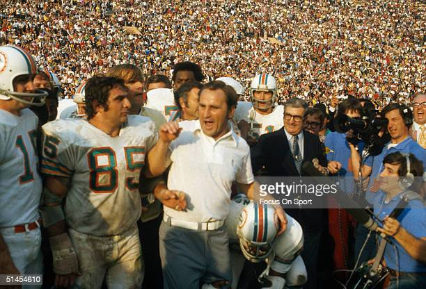 Don Shula coach of the Miami Dolphins talks to reporters while surrounded by his team on the field during the Super Bowl VIII against the Washington...