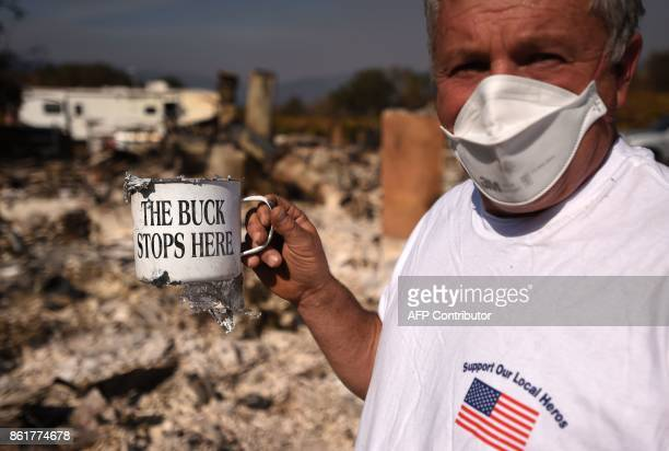 Don Summit holds up a surviving mug in front of his burned home in Redwood Valley California on October 15 2017 The death toll from California's...
