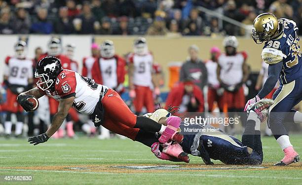 Don Unamba of the Winnipeg Blue Bombers grabs hold of Nik Lewis of the Calgary Stampeders in second half action in a CFL game at Investors Group...