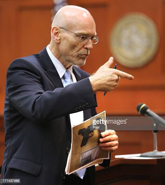 Don West a defense attorney for George Zimmerman makes a gun gesture describing the shooting of Trayvon Martin to the jury while holding the evidence...
