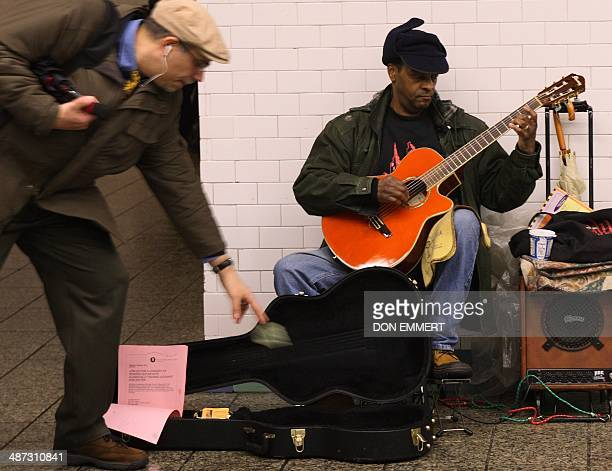 Don Witter Jr receives a tip while playing the guitar for commuters as they pass through the Times Square subway station on February 13 2008 in New...