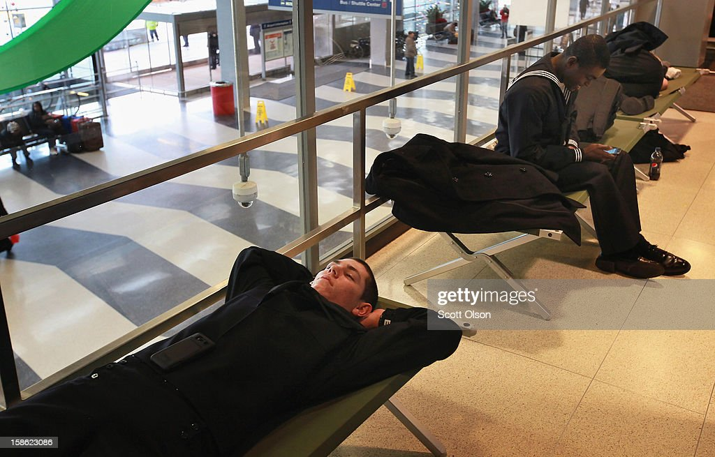 Donais Dayton (L) gets some rest on a cot in the hallway outside the USO as he waits to catch a flight home to Phoenix at O'Hare International Airport on December 21, 2012 in Chicago, Illinois. Today is the busiest air travel day of the Christmas holiday, with an estimated 200,000 travelers expected to travel through O'Hare today.