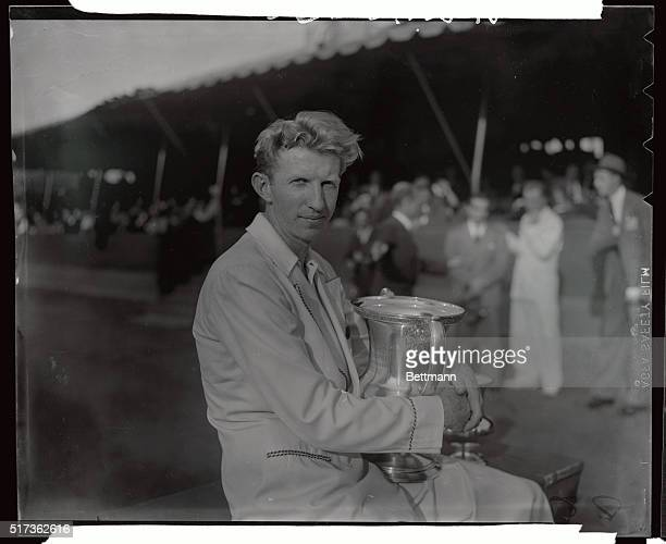 Donald Budge of California world's foremost tennis amateur is pictured above with the victor's trophy after defeating his fellowCalifornian Gene Mako...