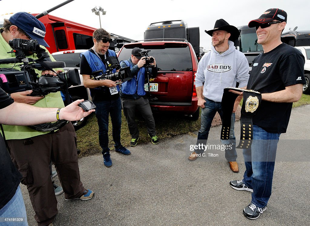 Donald 'Cowboy' Cerrone (2ndR) presents NASCAR driver <a gi-track='captionPersonalityLinkClicked' href=/galleries/search?phrase=Kevin+Harvick&family=editorial&specificpeople=209186 ng-click='$event.stopPropagation()'>Kevin Harvick</a> (R) with an UFC belt at Daytona International Speedway on February 22, 2014 in Daytona Beach, Florida.