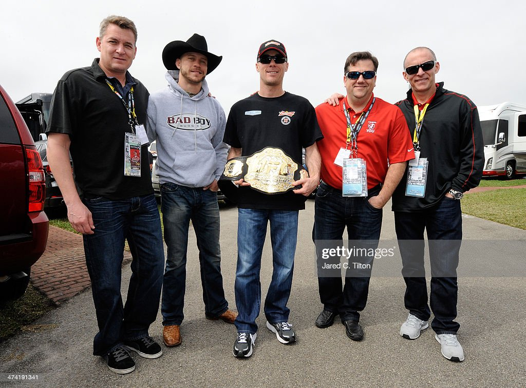 Donald 'Cowboy' Cerrone (2ndL) presents NASCAR driver <a gi-track='captionPersonalityLinkClicked' href=/galleries/search?phrase=Kevin+Harvick&family=editorial&specificpeople=209186 ng-click='$event.stopPropagation()'>Kevin Harvick</a> (C) with an UFC belt at Daytona International Speedway on February 22, 2014 in Daytona Beach, Florida.