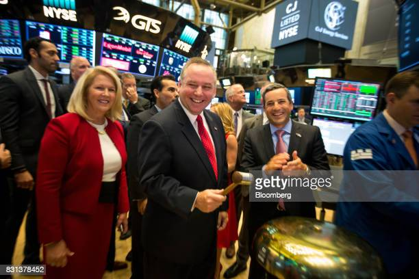 Donald Gawick president and chief executive officer of CJ Energy Services Inc center rings a ceremonial bell on the floor of the New York Stock...