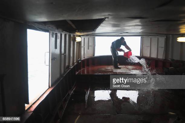 Donald Joyal washes down the deck of the Three Suns after a day of fishing on Lake Superior on March 26 2017 near Ironwood Michigan The Three Suns...