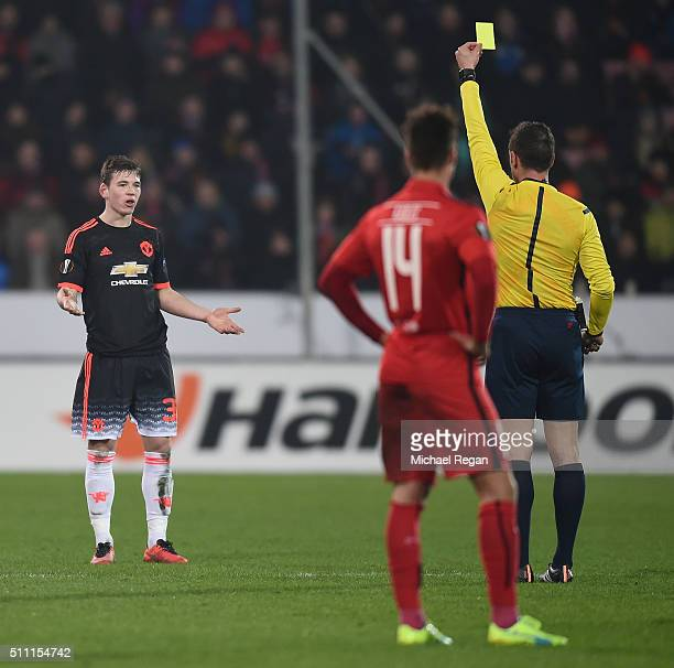 Donald Love of Manchester United is shown a yellow card by referee Artur Dias during the UEFA Europa League round of 32 first leg match between FC...