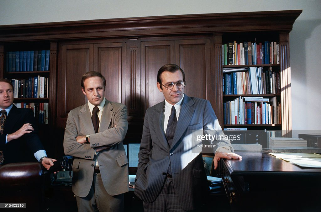 Donald Rumsfeld fingers his 'stand-up' desk in White House office 11/6 as he talks with his successor as White House Chief of Staff, Richard B. Cheney. Donald Rumsfeld has been nominated by President Ford to succeed Secretary of Defense James Schlesinger. Rumsfeld said he found 'stand-up' desk relaxing since many of his White House duties required him to sit down.