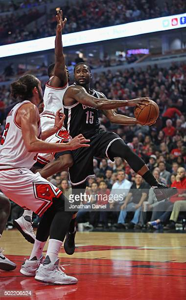 Donald Sloan of the Brooklyn Nets lepas to pass between Joakim Noah and Aaron Brooks of the Chicago Bulls at the United Center on December 21 2015 in...