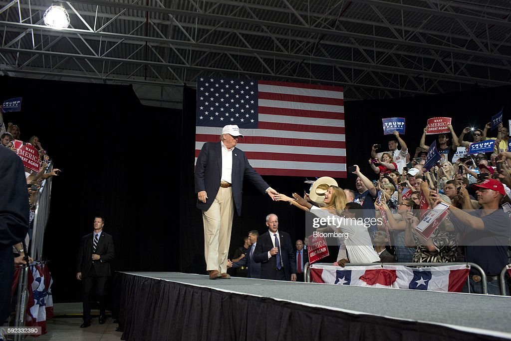 Donald Trump 2016 Republican presidential nominee greets supporters while arriving on stage during a campaign event in Lansing Michigan US on Friday...