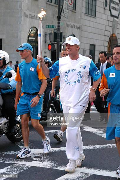 Donald Trump carries the Olympic flame during Day 15 of the Athens 2004 Olympic Torch Relay on June 19 2004 in New York New York The Olympic flame...