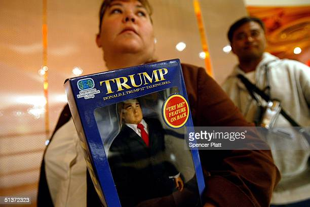 Donald Trump fan stands with the new Donald Trump 12inch talking doll September 29 2004 at the Toys 'R' Us store in New York City The doll's phrases...