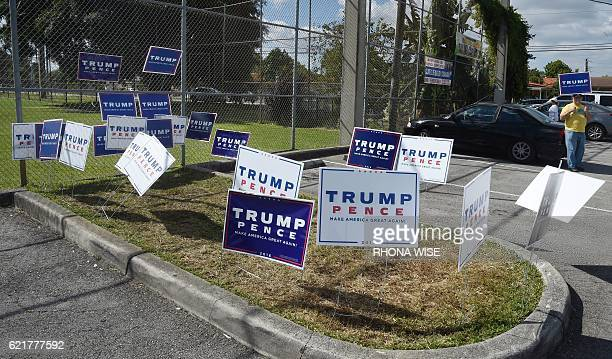 A Donald Trump for president supporter holds a sign at a polling center in Miami Florida on November 8 2016 / AFP / RHONA WISE