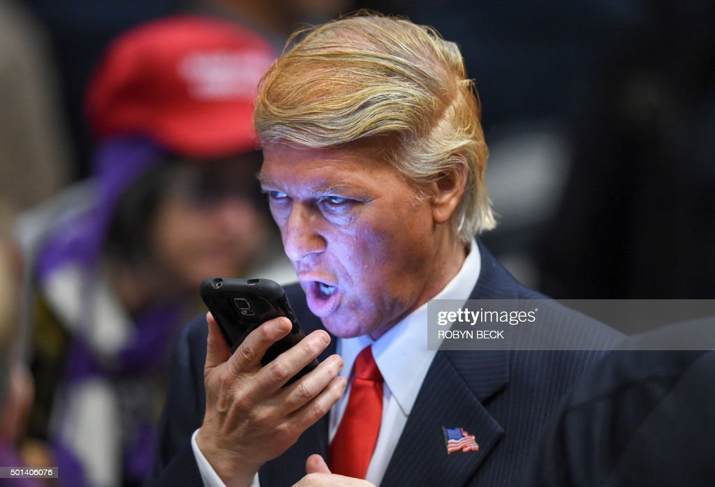 Donald Trump impersonator Robert S Ensler speaks on a phone before a rally by Republican presidential hopeful Donald Trump at the Westgate Hotel and...