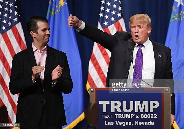 Donald Trump Jr looks on as his father Republican presidential candidate Donald Trump waves after speaking at a caucus night watch party at the...