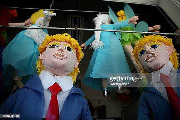 Donald Trump pinatas are displayed in the window at Pinata Art on August 28 2015 in San Francisco California Donald Trump pinatas are selling out at...