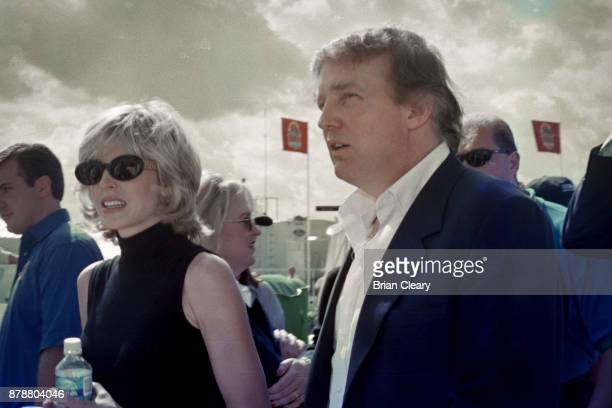 Donald Trump R walks in the pits with Marla Maples before before the Indy 200 Indy Racing League IRL race at Walt Disney World Speedway Speedway on...