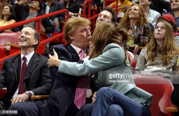 Donald Trump takes part of the Miami Heat 'Kiss Me Cam' tradition with his fiance Melania Knauss during the Miami Heat game against the Denver...