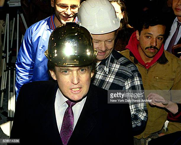 Donald Trump wearing a gold hard hat given to him by construction workers at the Trump Palace