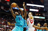 Donatas Motiejunas of the Houston Rockets battles for a rebound with Michael KiddGilchrist of the Charlotte Hornets during their game at the Toyota...