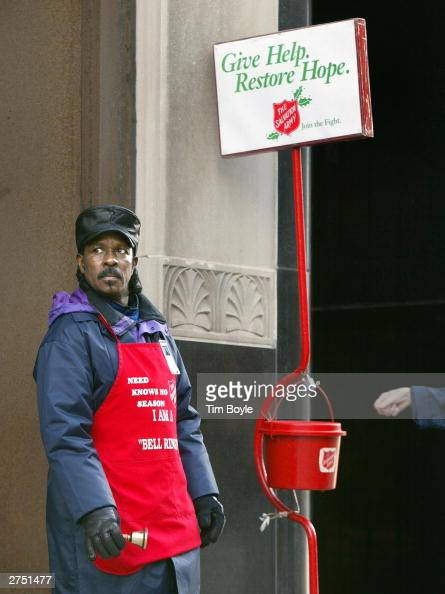 A donation is about to be dropped into the kettle of Salvation Army bell ringer Robert Walker outside a store on the Magnificent Mile November 21...
