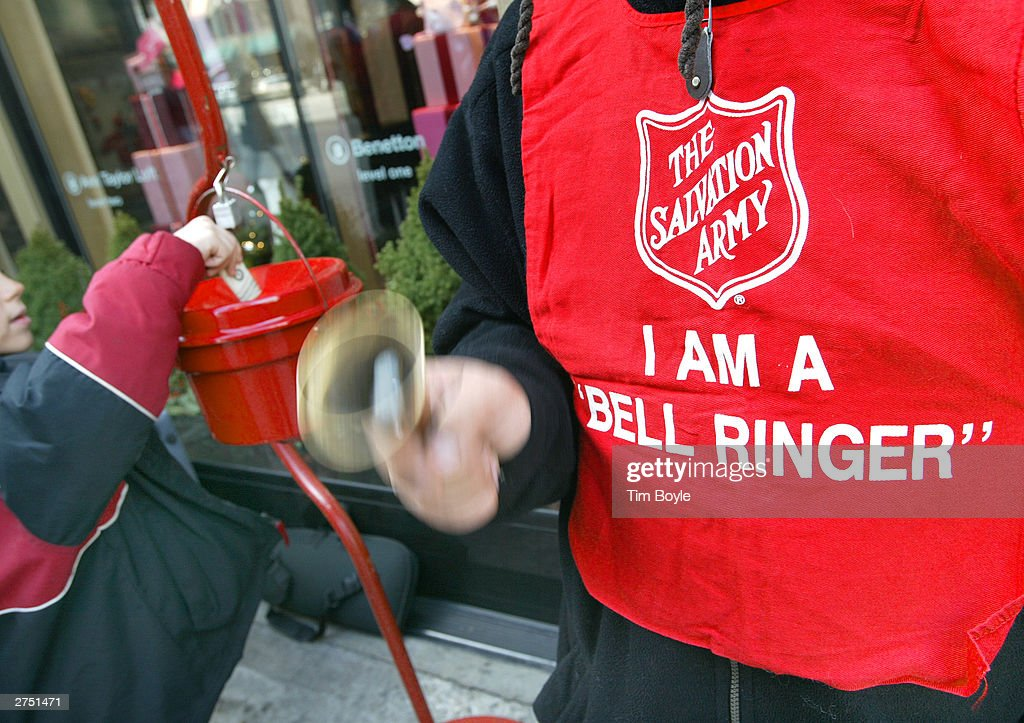 A donation is made as Salvation Army bell ringer Ruben Rios works outside a store November 21 2003 on the Magnificent Mile in Chicago Funds raised...