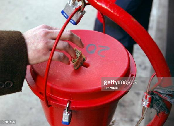 A donation is made into the kettle of Salvation Army bell ringer Robert Walker outside a store on the Magnificent Mile November 21 2003 in Chicago...