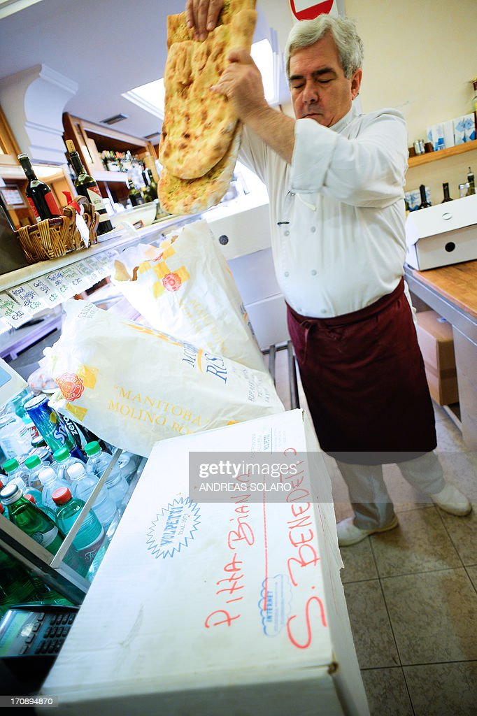 Donato Sarzarulo a manager at gourmet grocer Volpetti in Rome's trendy Testaccio neighbourhood prepares packs with food scraps in his shop to deliver...
