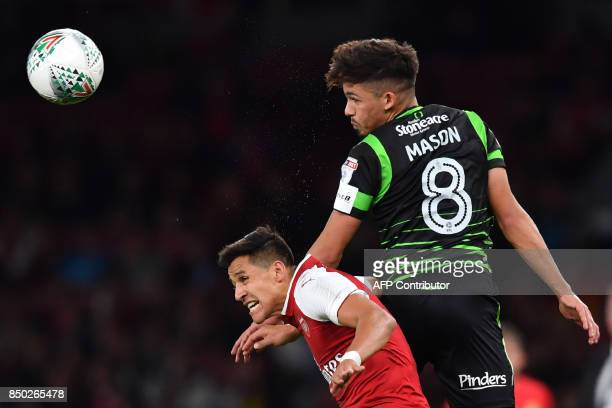 Doncaster Rovers' English midfielder Niall Mason wins a header from Arsenal's Chilean striker Alexis Sanchez during the English League Cup third...