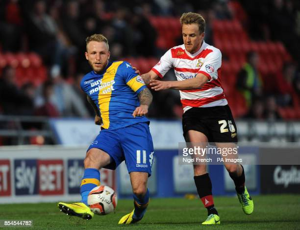 Doncaster Rover's James Coppinger and Derby County's Johnny Russell battle for the ball during the Sky Bet Championship match at the Keepmoat Stadium...