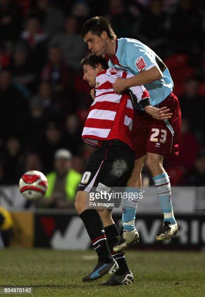 Doncaster Rovers' John Spicer and Burnley's Stephen Jordan battle for the ball during the CocaCola Championship match at Keepmoat Stadium Doncaster