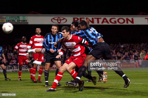 Doncaster Rovers' Nick Fenton is crowded out by Nottingham Forest's Wes Morgan and David Johnson