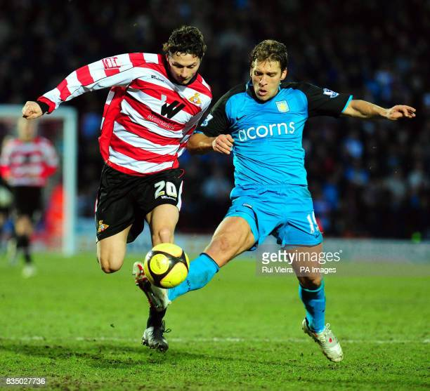 Doncaster's John Spicer and Aston Villa's Stylian Petrov during the FA Cup Fourth Round at Keepmoat Stadium Doncaster